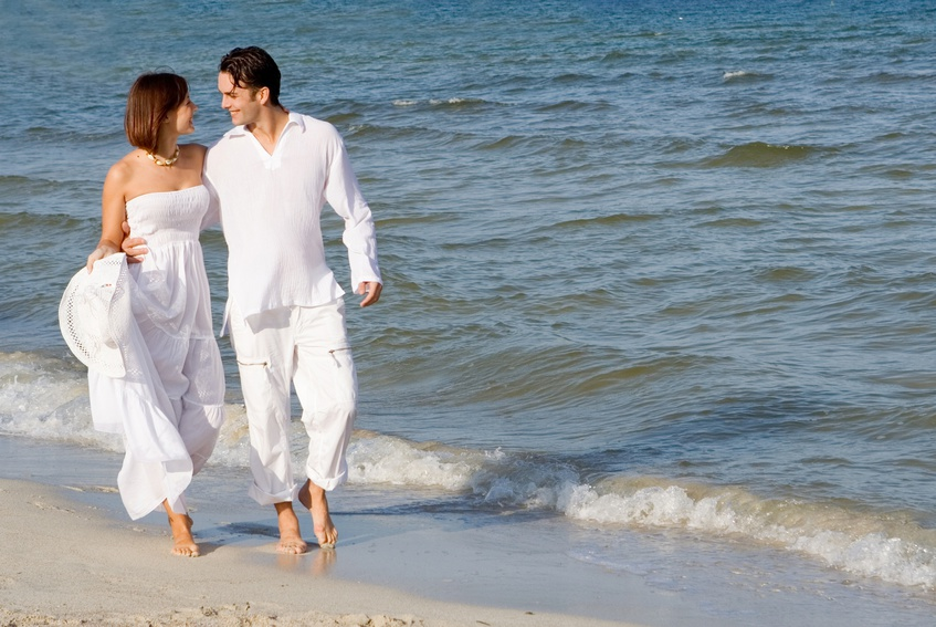happy wedding couple walking along seashore