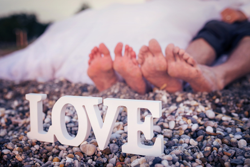 Los pies de l@s novi@s en la arena de la playa